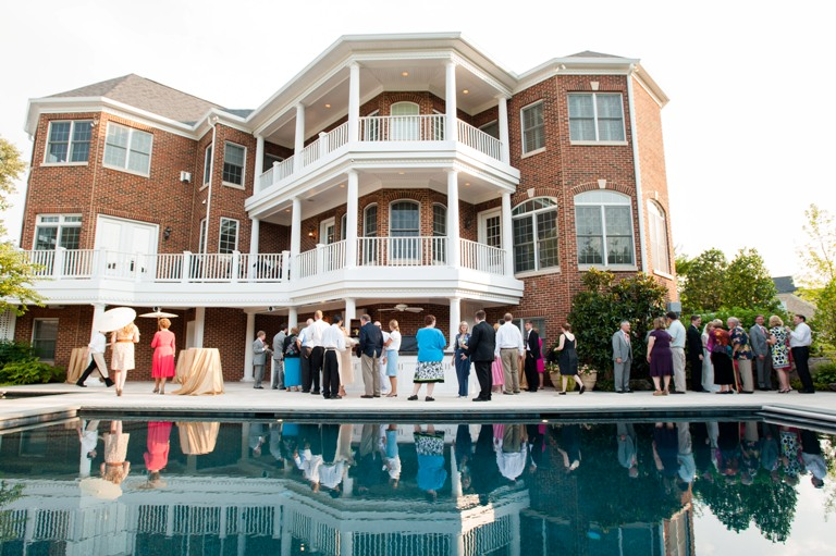 Guests congregate by an in-ground pool during the cocktail reception